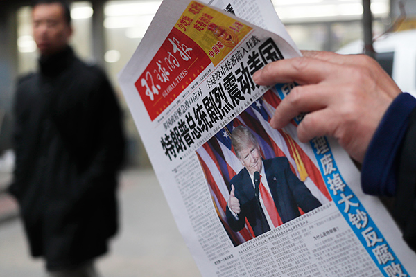 "FILE - In this Thursday, Nov. 10, 2016, file photo, a man reads a newspaper with the headline of ""U.S. President-elect Donald Trump delivers a mighty shock to America"" at a news stand in Beijing. Chinese President Xi Jinping has reaffirmed the importance of relations with the United States in a phone conversation with President-elect Donald Trump. Xi spoke by telephone with Trump on Monday in the first known communication between the two men. (AP Photo/Andy Wong, File)"