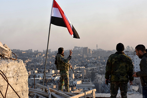 A Syrian government soldier gestures a v-sign under the Syrian national flag near a general view of eastern Aleppo after they took control of al-Sakhour neigbourhood in Aleppo, Syria in this handout picture provided by SANA on November 28, 2016. SANA/Handout via REUTERS ATTENTION EDITORS - THIS IMAGE WAS PROVIDED BY A THIRD PARTY. EDITORIAL USE ONLY. REUTERS IS UNABLE TO INDEPENDENTLY VERIFY THIS IMAGE. - RTSTSGY