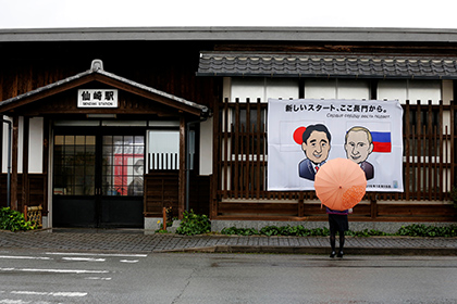 """A woman looks at a banner showing Japan's Prime Minister Shinzo Abe and Russian President Vladimir Putin at the Senzaki station in Nagato, Yamaguchi prefecture, Japan, December 14, 2016, a day before their summit meeting. The words on top read, """"A new start from here in Nagato""""."""