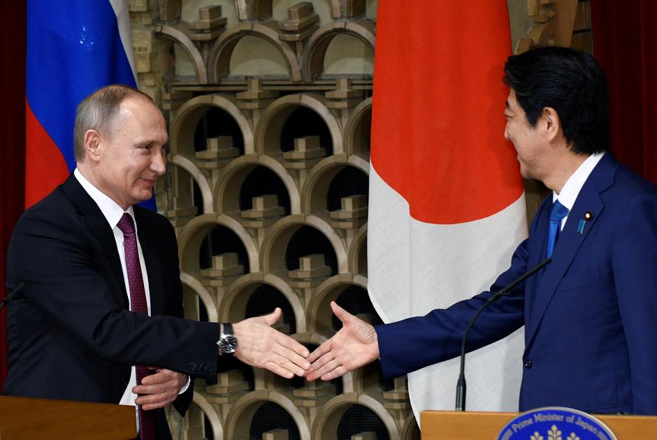 Владимир Путин и Синдзо Абэ пожимают руки в конце совместной пресс-конференции