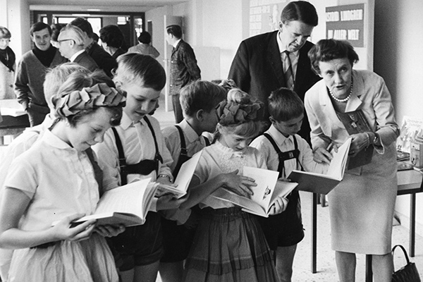 A new elementary school in West Berlin's Staaken (Spandau) district is named after world famous Swedish author Astrid Lindgren, right, sourrounded by pupils of the new school, reading books written by her, which she signs for them, April 18, 1966. Behind Lindgren is Heinz Evers, West Berlin's top government official in charge of the city's school system. (