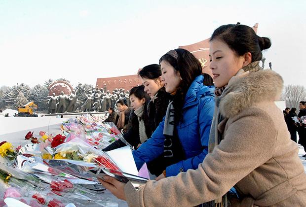 Граждане КНДР возлагают цветы к статуе Ким Ир Сена в Пхеньяне в первый день нового года