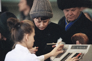 A woman pays for her groceries at the Tagansky supermarket in Moscow on Dec. 19, 1990 as a man waits behind her holding a load of bread. Food is more plentiful at farmers' markets than at state-run stores such as this, but prices are much higher.