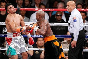 Floyd Mayweather, center, delivers a knockout punch to Victor Ortiz as referee Joe Cortez, right, looks on in the fourth round during a WBC welterweight title fight, Saturday, Sept. 17, 2011, in Las Vegas