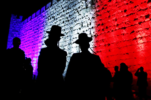 People walk past the walls of Jerusalem's Old City lit in blue, white and red, colours of the French flag, in solidarity with Paris, in Jerusalem November 15, 2015