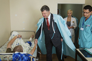 Ukrainian President Petro Poroshenko (2nd L) shakes hands with a serviceman, who was wounded during Monday's protest outside the parliament building, at the Ukrainian Interior Ministry's hospital in Kiev, Ukraine, September 1, 2015, in this handout photo provided by the Ukrainian Presidential Press Service. A fragile truce between Ukrainian government forces and pro-Russian separatists appeared to be holding on Tuesday as both sides made a renewed effort to silence their guns and make the much-abused ceasefire work. Two more guardsman have died from wounds sustained in violent protests outside Ukraine's parliament, the national guard said. One guardsman was reported on Monday as having been killed in the unrest and nearly 90 wounded.