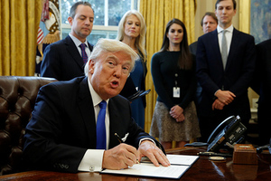 U.S. President Donald Trump looks up while signing an executive order to advance construction of the Keystone XL pipeline at the White House in Washington January 24, 2017.
