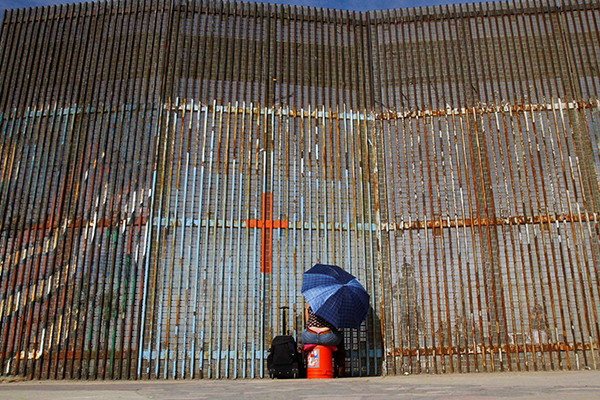 A woman talks to her relatives across a fence separating Mexico and the United States, in Tijuana, Mexico, November 12, 2016. REUTERS/Jorge Duenes TPX IMAGES OF THE DAY