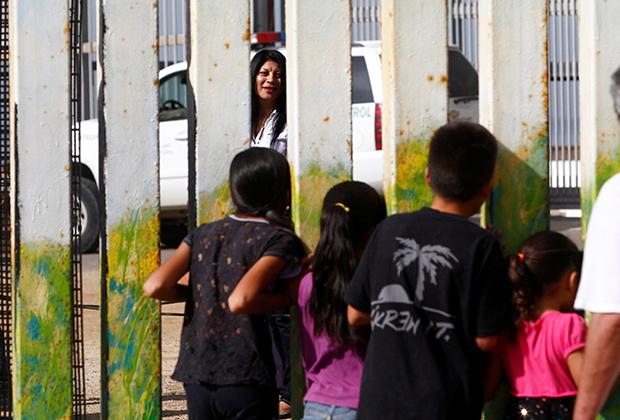 В парке Сан-Диего мать разговаривает через забор с детьми, находящимися в Тихуане
