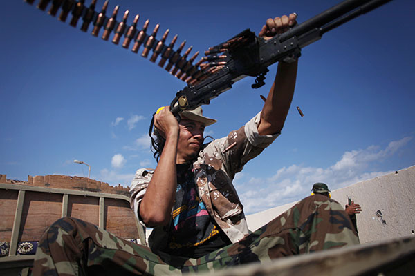 A revolutionary fighter fires at Gadhafi loyalists in downtown Sirte, Libya, Tuesday, Oct. 18, 2011. About 1,000 Libyan revolutionary troops have launched a major assault on Moammar Gadhafi's hometown, surging from the east to try to capture the last area under loyalist control.