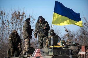 Ukrainian soldiers stand next to a Ukrainian national flag atop an armored vehicle