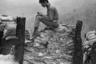 Южновьетнамский солдат использует несколько минут уединения, чтобы написать письмо, сидя на мешках с песком.