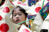 A girl is surrounded by samurai warrior helmets made of paper during an event celebrating the upcoming Children's Day at Sensoji temple in Tokyo April 20, 2007. Samurai warrior armours are traditional symbols of celebrations on Children's Day, which will take place on May 5.
