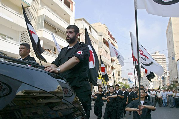 Lebanese members of the Syrian Social Nationalist Party, a pro-Syrian leftist Lebanese party, carry their party's flag during the funeral procession of Najib Mohammed Shams el-Din and Ali Mohammed Shams el-Din, in the port city of Tyre, southern Lebanon, Saturday, Aug. 19, 2006. Najib and Ali, two members of the Syrian Social Nationalist Party, were killed when an Israeli airstrike attack hit a building, where they were taking refuge, in Tyre mid July, a few days after the beginning of the Israeli offensive on Lebanon.