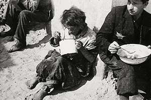 Man and woman eating from a pot and a pail on a street corner, 1940-1944