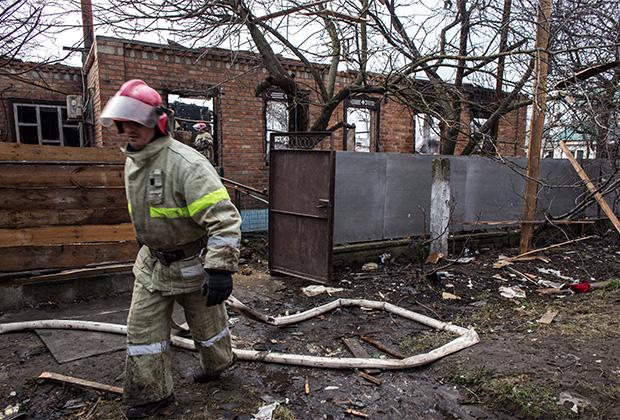 У разрушенного дома, пострадавшего в результате пожара на складах боеприпасов в Харьковской области