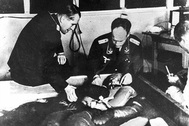 A cold water immersion experiment at Dachau concentration camp presided over by Professor Ernst Holzlöhner (left) and Dr. Sigmund Rascher (right). The subject is wearing an experimental Luftwaffe garment