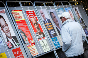 A man looks at campaign posters of the 11th candidates who run in the 2017 French presidential election in Enghien-les-Bains, near Paris, France April 19, 2017