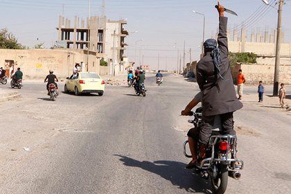 A man holds up a knife as he rides on the back of a motorcycle touring the streets of Tabqa city with others in celebration after Islamic State militants took over Tabqa air base, in nearby Raqqa city August 24, 2014. Islamic State militants stormed the air base in northeast Syria on Sunday, capturing most of it from government forces after days of fighting over the strategic location, a witness and a monitoring group said. Fighting raged inside the walls of the Tabqa air base, the Syrian army's last foothold in an area otherwise controlled by IS, which has seized large areas of Syria and Iraq.