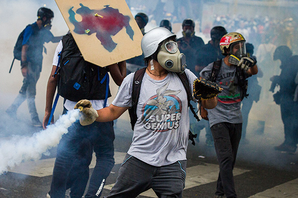 An opposition activist hurls back at riot police a tear gas canister during clashes ensuing a protest against President Nicolas Maduro, in Caracas on May 8, 2017. Venezuela's opposition mobilized Monday in fresh street protests against President Nicolas Maduro's efforts to reform the constitution in a deadly political crisis. Supporters of the opposition Democratic Unity Roundtable (MUD) gathered in eastern Caracas to march to the education ministry under the slogan ''No to the dictatorship.