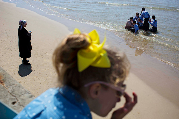 Ultra-Orthodox Jewish women enjoy the beach at the Mediterranean Sea beach front during the last vacation day of the Jewish Passover holiday, in Tel Aviv, Israel, Tuesday, April 22, 2014. (AP Photo/Oded Balilty)