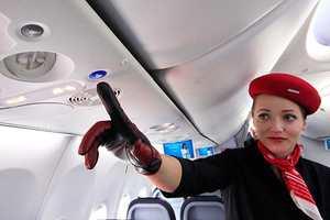 An airberlin stewardess shows the new call button in the Boeing 737 during 49th Paris Air Show at the Le Bourget Airport, near Paris June 21, 2011. The new interior design for Boeing's 737 passenger jet, the best-selling plane in aviation history, includes an innovation that is as radical as it is obvious: a flight attendant button that is situated well away from the reading light button and actually looks different from it. The Paris Air Show runs from June 20-26. REUTERS/Pascal Rossignol (FRANCE - Tags: BUSINESS TRANSPORT)