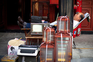 An antique shop owner naps on a chair outside his shop at a market in Beijing, China, Monday, Aug. 23, 2010. (AP Photo/Alexander F. Yuan)