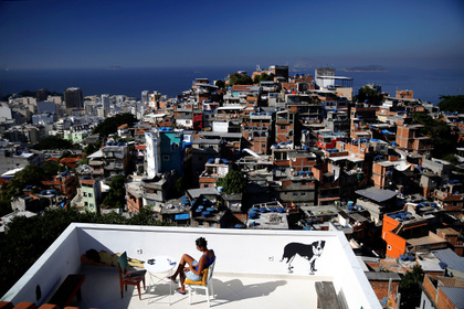 """A woman sits on a terrace at Tiki hostel in Cantagalo favela, in Rio de Janeiro, Brazil, April 16, 2016. Hostels in a few of RioÕs more than 1,000 slums serve not only as a cheap housing alternative for the more adventurous among the estimated 500,000 foreign tourists expected to arrive for the Olympics in August. The establishments also open up the rich culture of the city's shantytowns for travellers, giving them a glimpse into once """"no-go"""" areas where about one-fifth of Rio's population lives. REUTERS/Pilar Olivares SEARCH """"HOLIDAY FAVELAS"""" FOR THIS STORY. SEARCH """"THE WIDER IMAGE"""" FOR ALL STORIES TPX IMAGES OF THE DAY"""