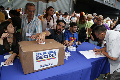 CARACAS, July 17, 2017 A man casts his vote during the referendum called by the Democratic Unity Roundtable, in Caracas, Venezuela, on July 16, 2017. Venezuela saw its feuding political factions both prepare polls on Sunday, with the government holding a simulation of the July 30 vote to elect the ANC while the opposition was organizing an unofficial referendum of its own to gauge public support or rejection for the ANC. dtf) (Credit Image: Global Look Press via ZUMA Press) Photographer: © Boris Vergara