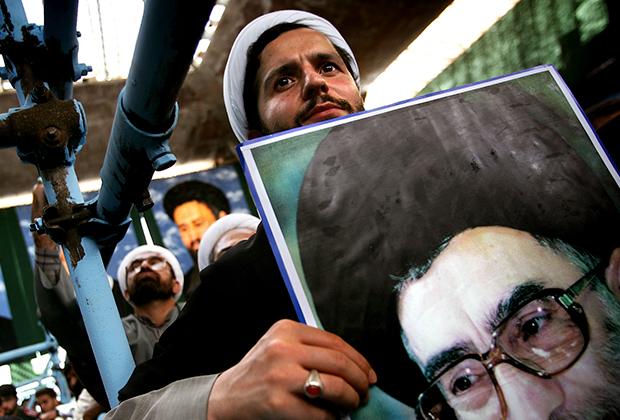 Иранский богослов с портретом Хаменеи в руках