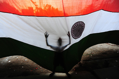 A boy tries to control an Indian national flag from the wind as it is installed at a wholesale market on the occasion of India's Independence Day celebrations in the southern Indian city of Chennai August 15, 2012. REUTERS/Babu (INDIA - Tags: SOCIETY ANNIVERSARY TPX IMAGES OF THE DAY)