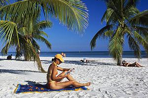 Woman reading, sandy beach, palm trees, Smathers Beach, Key West, The Keys, Florida, USA