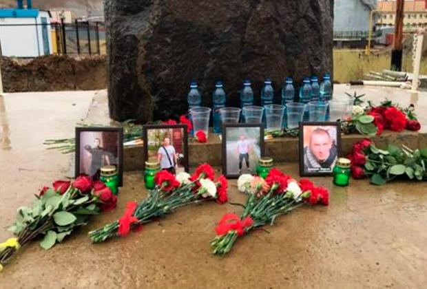 Люди приносят цветы к памятному камню у рудника «Мир», чтобы почтить память погибших шахтеров