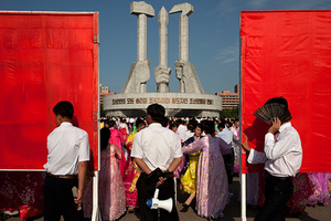 North Korean men hold propaganda billboards while a supervisor, center, watches folk dancing held in front of the Monument to Party Founding in Pyongyang, North Korea, Wednesday, June 19, 2013. The dancing performance was held to celebrate the day North Korea's late leader Kim Jong Il began his work at the central committee of the communist nation's ruling Workers' Party in 1964.