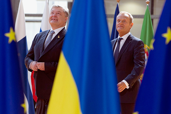 Ukrainian President Petro Poroshenko, left, and European Council President Donald Tusk walk between the EU and Ukrainian flags