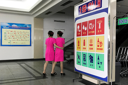 In this Monday, June 19, 2017, photo, staff at the Pothonggang department store walk towards an escalator in Pyongyang, North Korea. (AP Photo/Wong Maye-E)