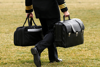 "A military aide, carrying the ""football"" containing launch codes for nuclear weapons, accompanies U.S. President Donald Trump onto Marine One upon Trump's departure from the White House in Washington, U.S. February 3, 2017. REUTERS/Kevin Lamarque"
