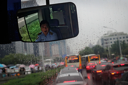 A city bus driver yawns as motorists are clogged with heavy traffic on a road on a rainy day in Beijing, Wednesday, July 26, 2017. Although China's capital is in a semi-dry climate, it receives much of its annual precipitation during the summer months. (AP Photo/Andy Wong)  Use
