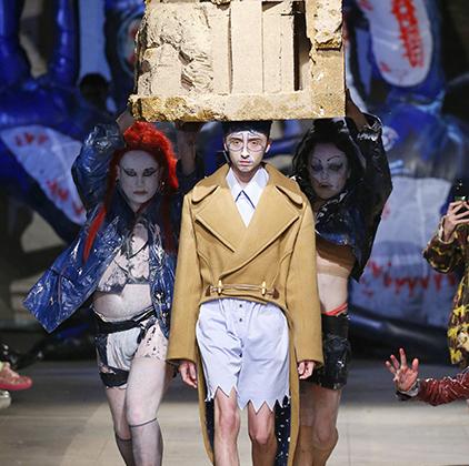 Центральный выход стал апогеем показа Чарльза Джеффри: двое довольно-таки тучных, по меркам модельного бизнеса, мужчин в масках и прозрачных гольфах тащили над головой модели нечто весьма напоминающее бетонный блок. Сам манекенщик при этом был одет в постмодернистский гибрид косухи и фрака.