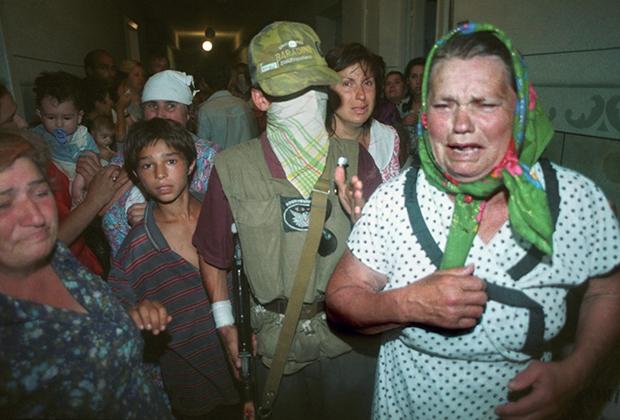 Закрывшие свои лица чеченские боевики Шамиля Басаева показывают журналистам женщин и детей, взятых ими в заложники при захвате больницы