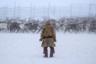 Оленевод в национальной саамской одежде в загоне для оленей.