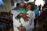 Прихожанка прощается со священником, который покидает Бока Колорадо — скорее всего, навсегда.