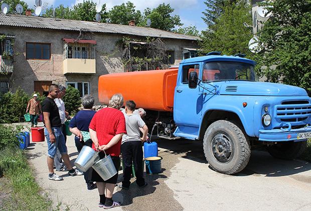 Жители города Старый Крым набирают в емкости питьевую воду, привезенную в цистернах