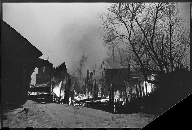 На путях отступления немцев в районе Гатчины горят подожженные гитлеровцами дома на Красной улице, переименованной немцами в Штутгартштрассе. Ленинградский фронт, 1943 год.