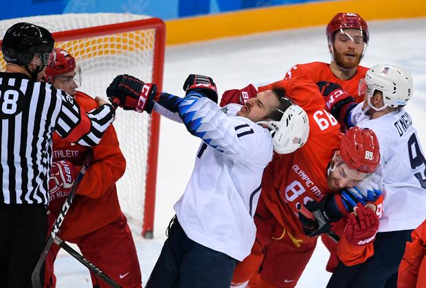 В центре: Гаррет Рой (США), справа на первом плане: Никита Нестеров (Россия) в матче Россия — США по хоккею среди мужчин группового этапа на XXIII зимних Олимпийских играх