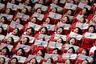 Болельщицы из Северной Кореи. В руках каждой флажок с Корейским полуостровом. За плечами — бдительный сосед.