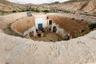 Берберы Джебель-Дахары научились строить подземные жилища больше тысячи лет назад. Каждый дом, по сути, представлял собой систему искусственных пещер, прорытых в мягком песчанике. Сначала копали большую яму — семь метров в глубину, десять в ширину. Она служила внутренним двориком. Затем строители углублялись в ее стены и проделывали в песчанике все необходимые помещения.