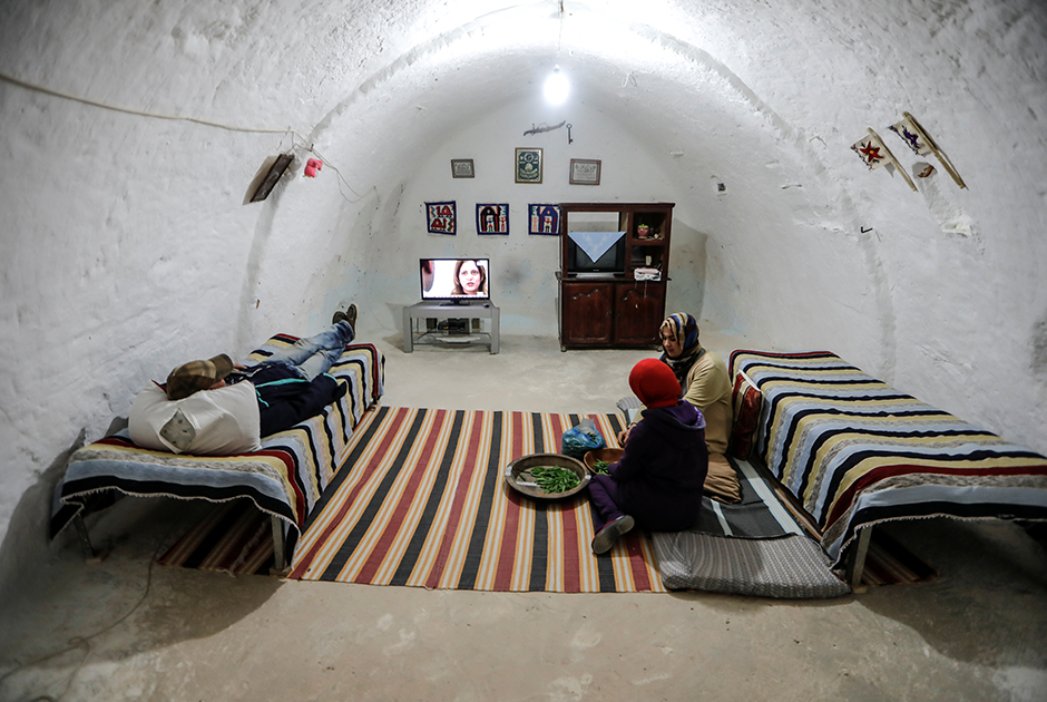 38-летняя Латифа Бен Яхия с дочерью чистят горох, пока сын смотрит телевизор