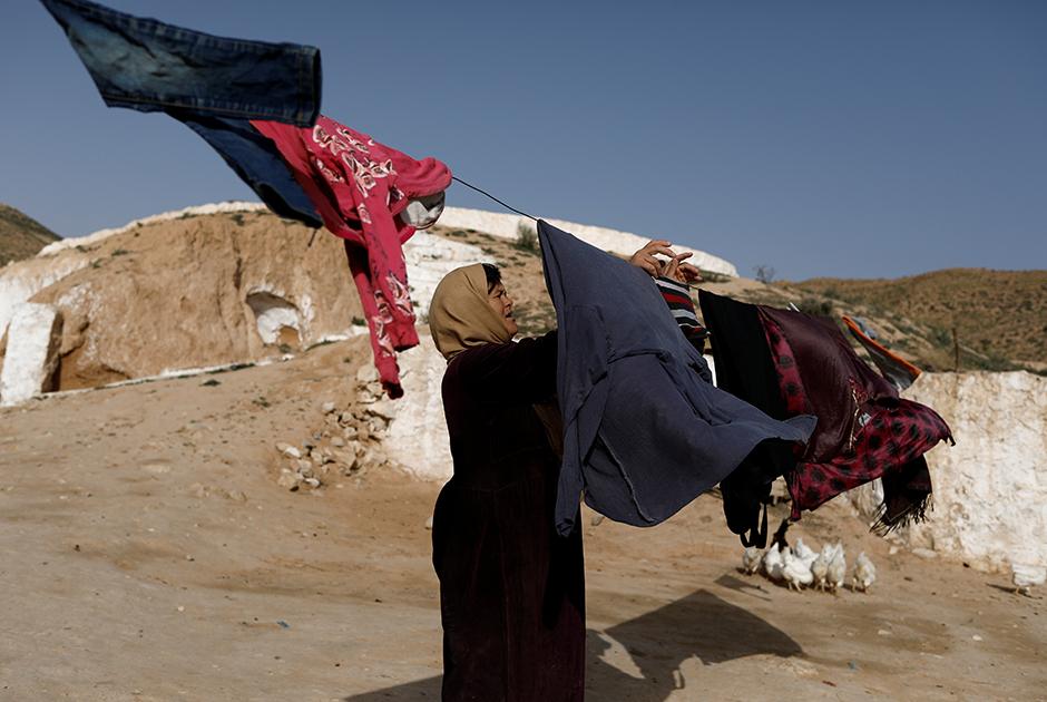 Салиха Мохамеди сушит постиранную одежду у подземного жилища в Матмате