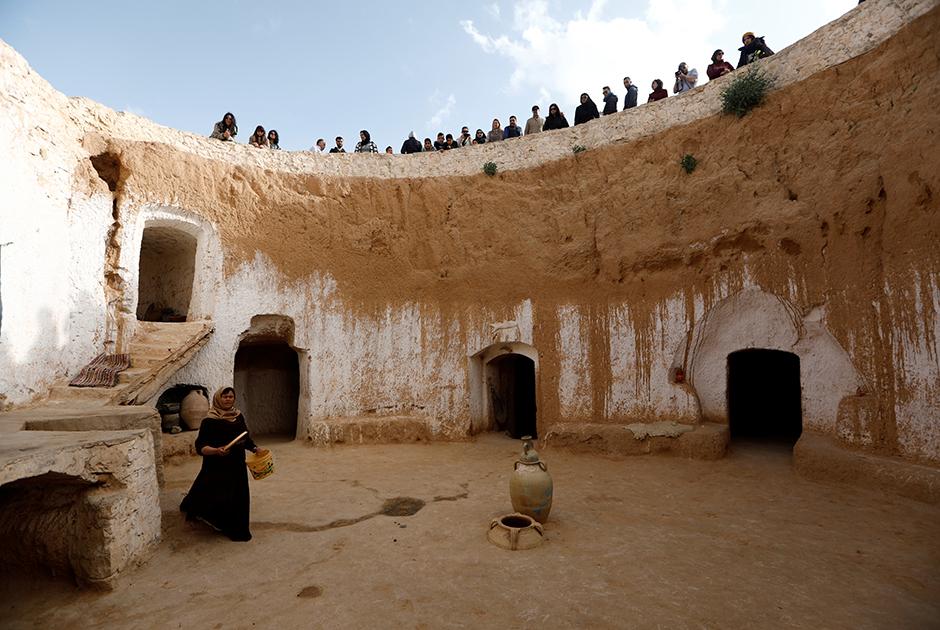 Туристы смотрят, как Салиха Мохамеди работает во дворе своего подземного жилища в Матмате